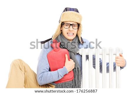 Chilled young man with hot water bottle hugging a radiator isolated on white background - stock photo