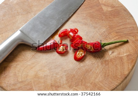 Chilli pepper and Knife on wooden bamboo chopping board - stock photo