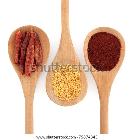 Chilli selection of powder, seed, and dried in skin, in three wooden spoons, over white background. - stock photo