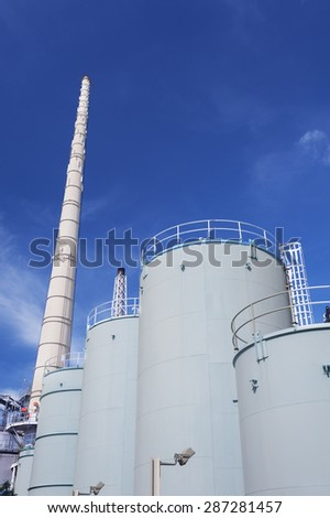 Chimney and oil tank in petrochemical plant  - stock photo