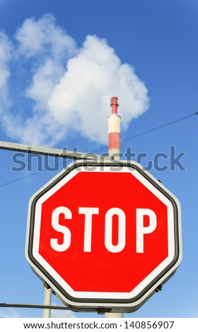 chimney of an industrial company and stop sign. symbolic photo for environmental protection and ozone. - stock photo