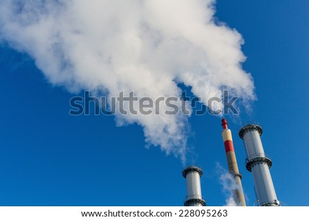 chimney of an industrial company with a strong smoke. symbol photo for environmental protection and ozone. - stock photo