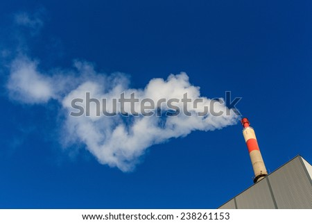 chimney of an industrial company with strong smoke. symbolic photo for environmental protection and ozone. - stock photo