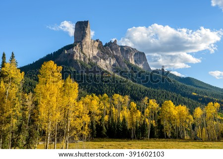 Chimney Peak - Evening view of Chimney Peak rock formations, 11,781 ft (3,591 m), surrounded by golden autumn aspen trees, near the summit of Owl Creek Pass, 10,114 ft (3,083m). - stock photo