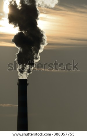 chimney pollutes the air and obscures the sun - stock photo