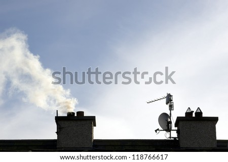 chimney stacks on estate house with smoke rising on a winters evening - stock photo