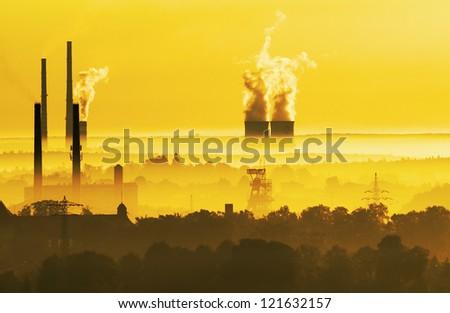 Chimneys of industry in morning light - stock photo