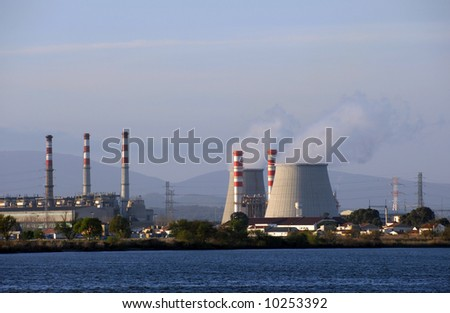 Chimneys of nuclear power plant, cooling towers emitting steam - stock photo