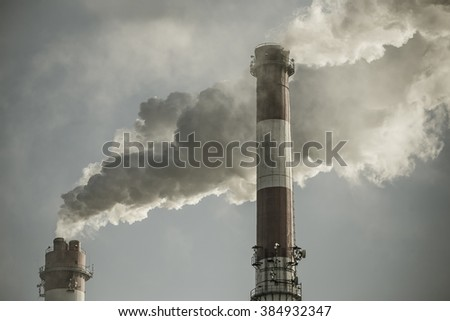 Chimneys with dramatic clouds of smoke, example of pollution on the environment. Cold tone. - stock photo