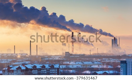 chimneys with smoke in the city at morning - stock photo
