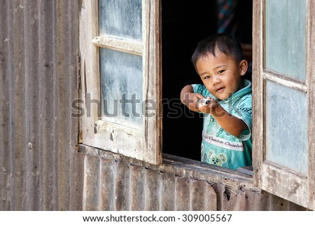 CHIN STATE, MYANMAR - JUNE 18 2015: Cute young boy in window in the recently opened for tourists Chin State Mountainous Region, Myanmar (Burma) - stock photo