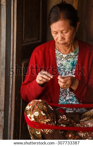 CHIN STATE, MYANMAR - JUNE 18 2015: Lady weaving with wool in the recently opened for tourists Chin State Mountainous Region, Myanmar (Burma) - stock photo