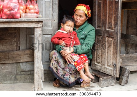 CHIN STATE, MYANMAR - JUNE 23 2015: Mother holding child in village popular for selling apples in the recently opened to foreigners area of Chin State - western Myanmar (Burma) - stock photo