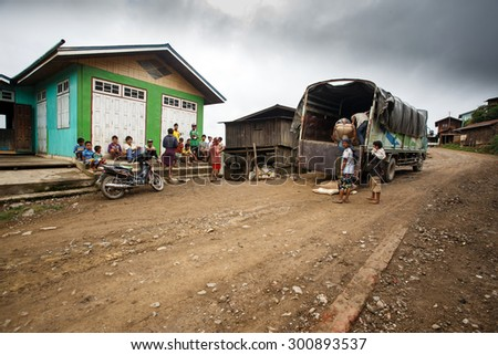 CHIN STATE, MYANMAR - JUNE 22 2015: Transporting goods through a village in the only recently opened for tourists Chin State Mountainous Region, Myanmar (Burma) - stock photo
