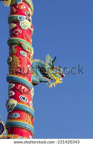 China Dragon Climb up and  entwine around pillar.Background is clear blue sky. - stock photo