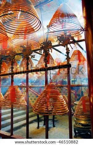 China, Hong Kong, sun light through incense coils in the ancient Man Mo temple - stock photo