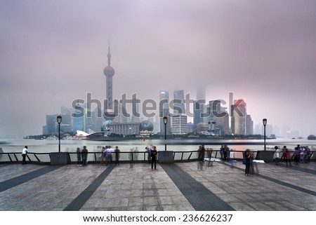 China SHanghai Pudong CBD sunset view over river illuminated skyscrapers and towers covered by pollution smog - stock photo