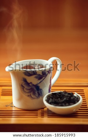 china teapot with fresh hot black tea on wooden tray - stock photo