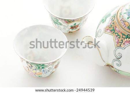 Chinaware tea pod and small drinking bowls - stock photo