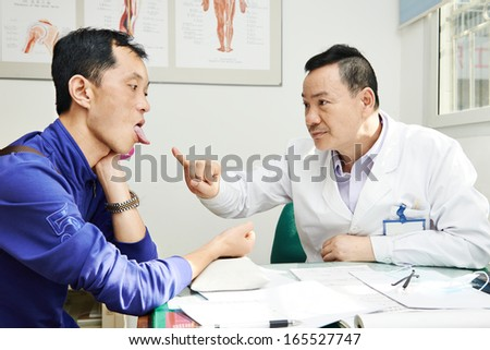 Chinese adult asian male doctor in clinic during tongue diagnosis - stock photo