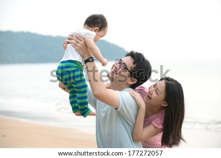 chinese asian family playing on the beach  - stock photo