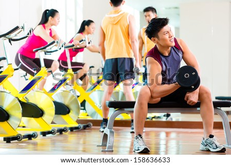 Chinese Asian group of men and woman doing sport exercise or training in fitness gym with barbell and weights for more power - stock photo