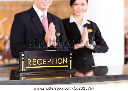 Chinese Asian reception team at luxury hotel front desk welcoming guests with typical gesture, a sign of good service and hospitality - stock photo