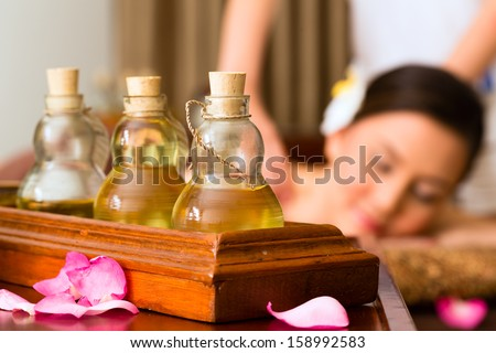 Chinese Asian woman in wellness beauty spa having aroma therapy massage with essential oil, looking relaxed - stock photo