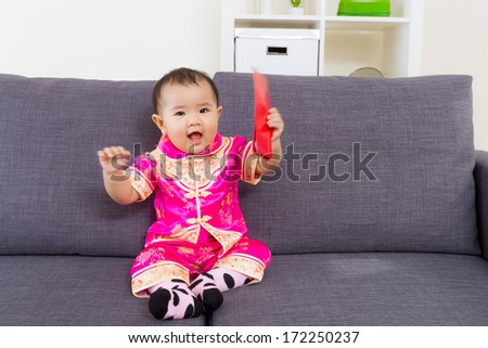 Chinese baby holding red pocket - stock photo