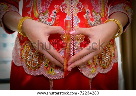 Chinese bride in traditional chinese wedding dress with heart shaped gesture - stock photo