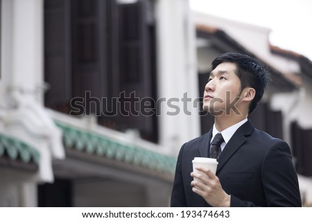Chinese business man in Asian city. Asian businessman smiling & looking away with blurred Chinese heritage building in background. - stock photo