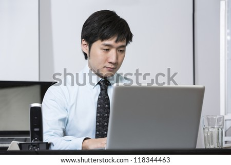 Chinese business man working on his laptop in an office. - stock photo