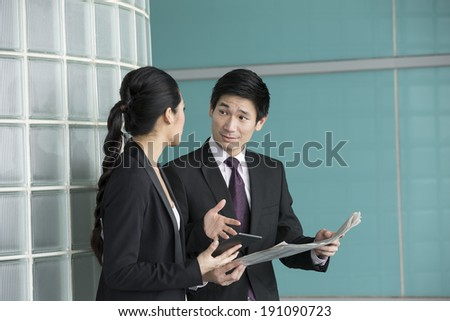 Chinese Business people reading electronic tablet and newspaper. Asian Business man and woman discussing current affairs. - stock photo