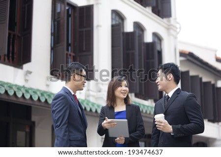 Chinese Business team meeting outside with tablet with blurred Chinese heritage building in background. - stock photo