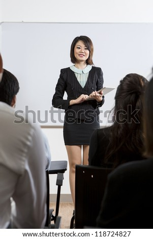 Chinese Business woman discussing information shown on a Digital Tablet - stock photo