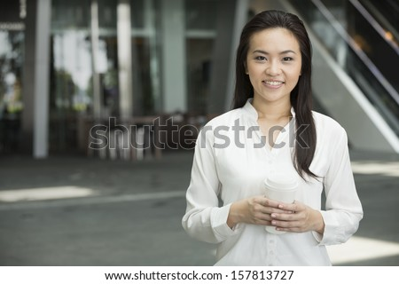 Chinese business woman in modern Asian city. Asian businesswoman smiling & looking at the camera with blurred office buildings as a background. - stock photo