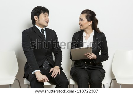 Chinese business woman interviewing an uncomfortable looking male applicant. - stock photo
