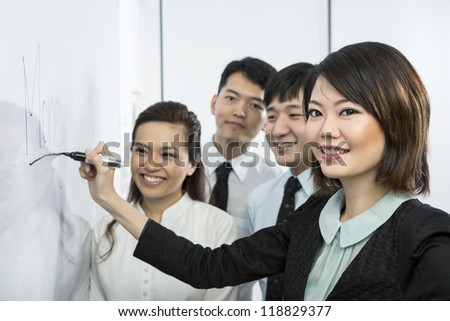 Chinese business woman writing 'Money' on a whiteboard with her team around her. - stock photo