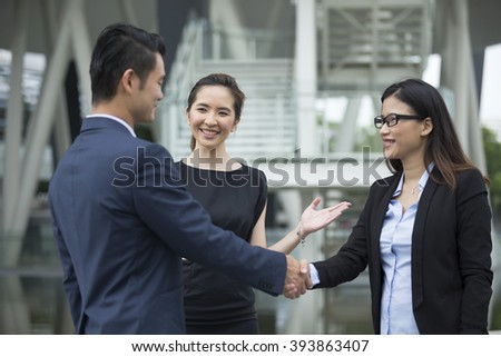 Chinese Businessman and businesswoman shaking hands outside the office. - stock photo