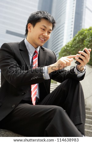 Chinese Businessman Dialling On Mobile Phone Outside Office - stock photo