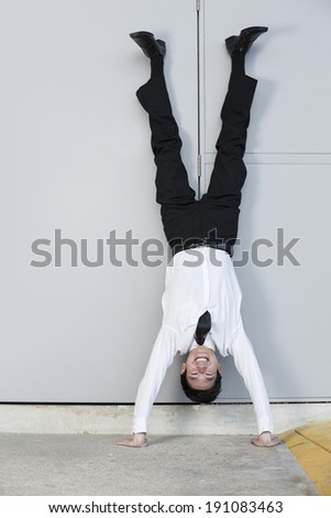 Chinese Businessman doing handstand outdoors. Conceptual business image - stock photo