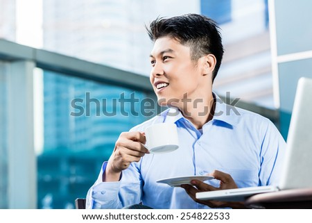 Chinese businessman having coffee at his laptop sitting in front of city skyline - stock photo