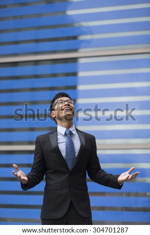 Chinese businessman outside office building with his arms raised celebrating his success. Concept about a freedom and achievement. - stock photo