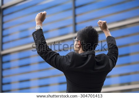 Chinese businessman outside office building with his arms raised celebrating his success. Concept about a freedom and achievement.