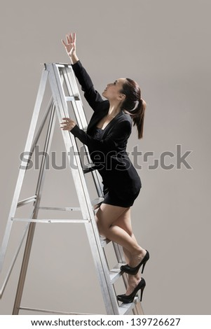 Chinese businesswoman wearing a dark suit and climbing a ladder. Conceptual image about ambition and success. - stock photo