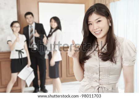 Chinese businesswoman with her thumb up smiling to camera in the office - stock photo