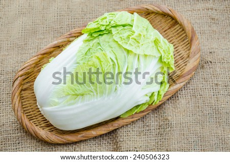 Chinese cabbage in weave basket on sack background - stock photo
