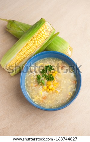 Chinese chicken and corn soup with fresh corn cob on the side. - stock photo