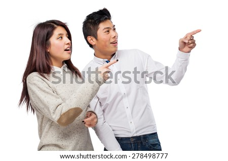 chinese couple pointing copyspace - stock photo