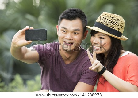 Chinese Couple taking a picture of themselves with smartphone - stock photo